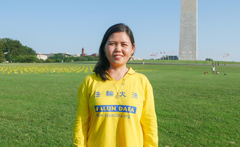 2021年7月16日傍晚,法輪功學員王福花在華盛頓紀念碑前準備參加燭光夜悼。(李辰/大紀元)