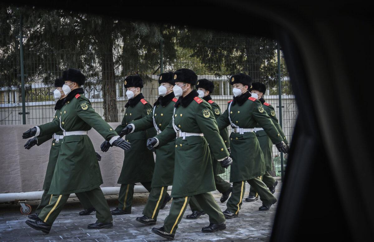 圖為2020年2月3日,中國北京,警察戴著口罩在換崗期間列隊行進。(Kevin Frayer/Getty Images)