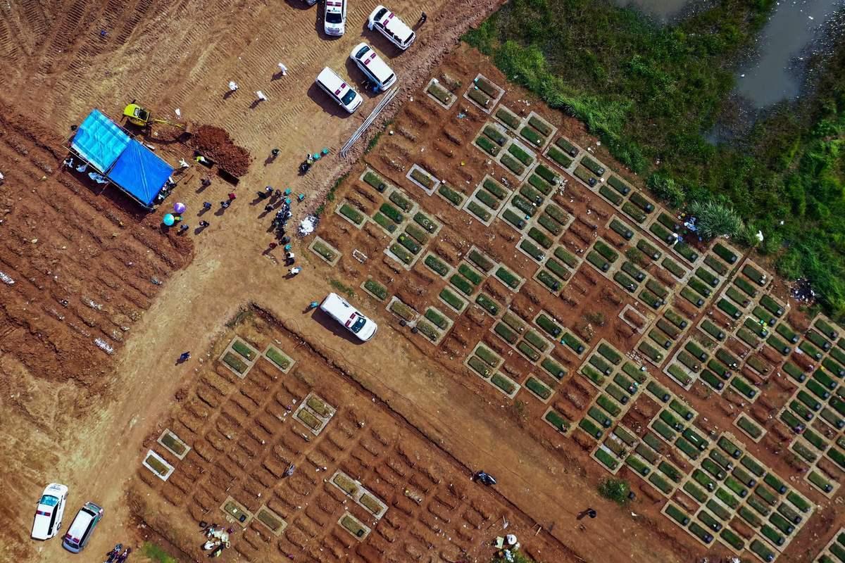 2021年7月7日,工人在西爪哇省的Pedurenan公墓埋葬Covid-19罹難者的遺體。(BAGUS SARAGIH/AFP via Getty Images)