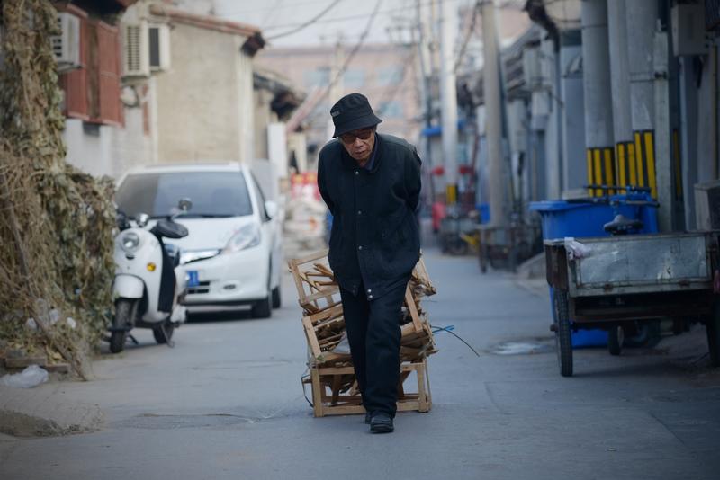 調查顯示大陸一線員工因工作繁重,反對延遲退休的佔比最高。圖為,北京街頭一拉著木箱的老人。(WANG ZHAO/AFP/Getty Images)