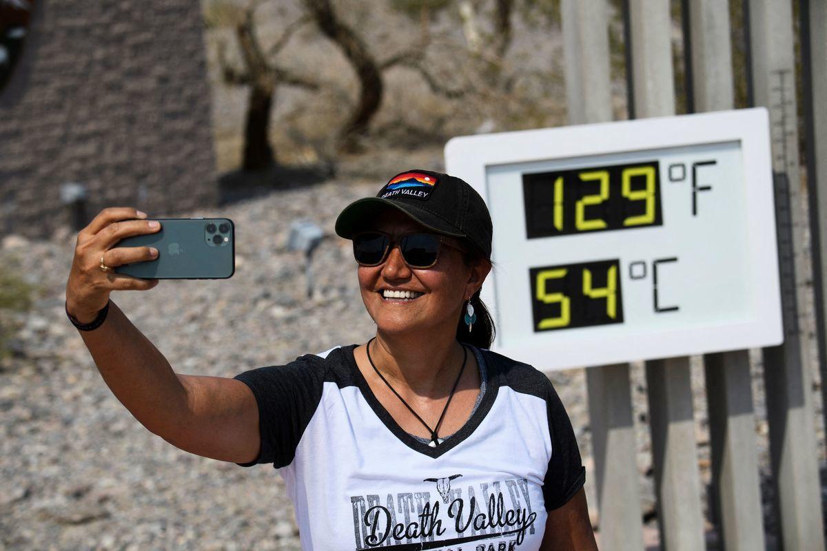 6月16日,以炎熱天氣著稱的加州死亡谷國家公園氣溫達到華氏129度,距離歷史最高紀錄只差5度。圖為2021年6月17日,遊客在加州死亡谷國家公園的Furnace Creek遊客中心與溫度計合照留念。(PATRICK T. FALLON/AFP via Getty Images)