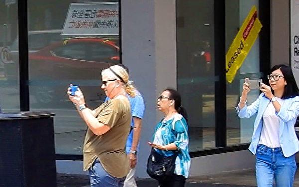 「解體中共」車隊在阿德萊德唐人街附近駛過時,不斷有路人豎起大拇指,大聲讀出標語叫好,也有的掏出手機搶拍。(楊陽/大紀元)