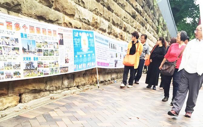 中國大陸遊客在澳洲悉尼歌劇院景點看法輪功真相展板。(明慧網)