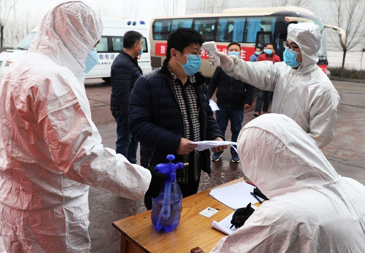 中共隱匿疫情,才導致病毒的大流行。圖為上班前量體溫的中國勞工。(STR/AFP via Getty Images)