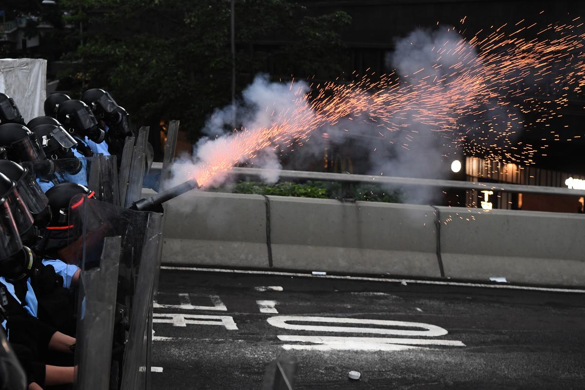 現場有記者採訪時被警察以近距離發射催淚彈、警棍痛擊等方式對待。香港記者協會發表聲明,嚴重譴責香港警方危害記者安全及損害新聞自由的行為。 (Anthony WALLACE / AFP)