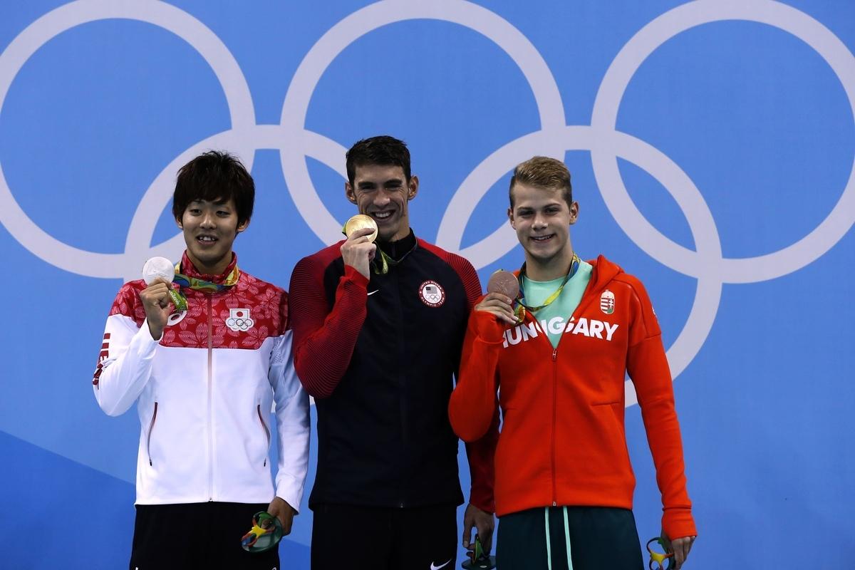 「飛魚」菲比斯(Michael Phelps)(中)和銀牌得主日本選手阪井聖人(左)及銅牌得主匈牙利泳將Tamas Kenderesi在領獎台上。(Odd ANDERSEN/AFP)