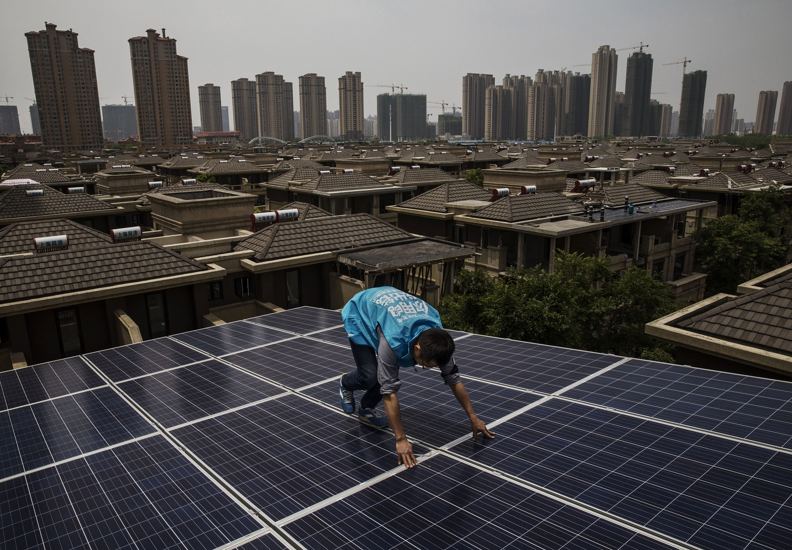 圖為2017年4月,工人在武漢市的一棟高樓上安裝光伏面板。(Photo by Kevin Frayer/Getty Images)