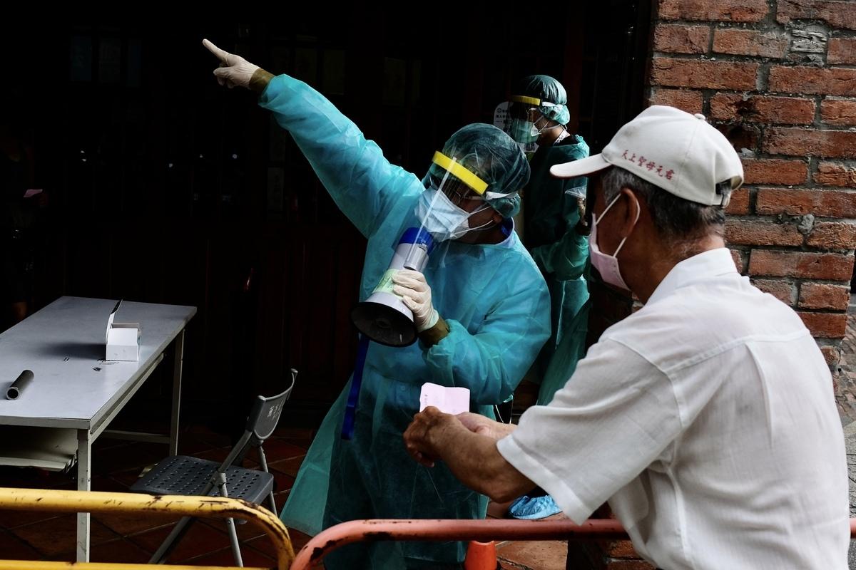 日本作家木下諄一認為,台灣目前雖然本土確診人數最近不斷激增,但台灣有2個防疫關鍵值得嘉許。圖為2021年5月18日,台北市萬華區民眾在篩檢前聽醫護人員的講解。(SAM YEH/AFP via Getty Images)