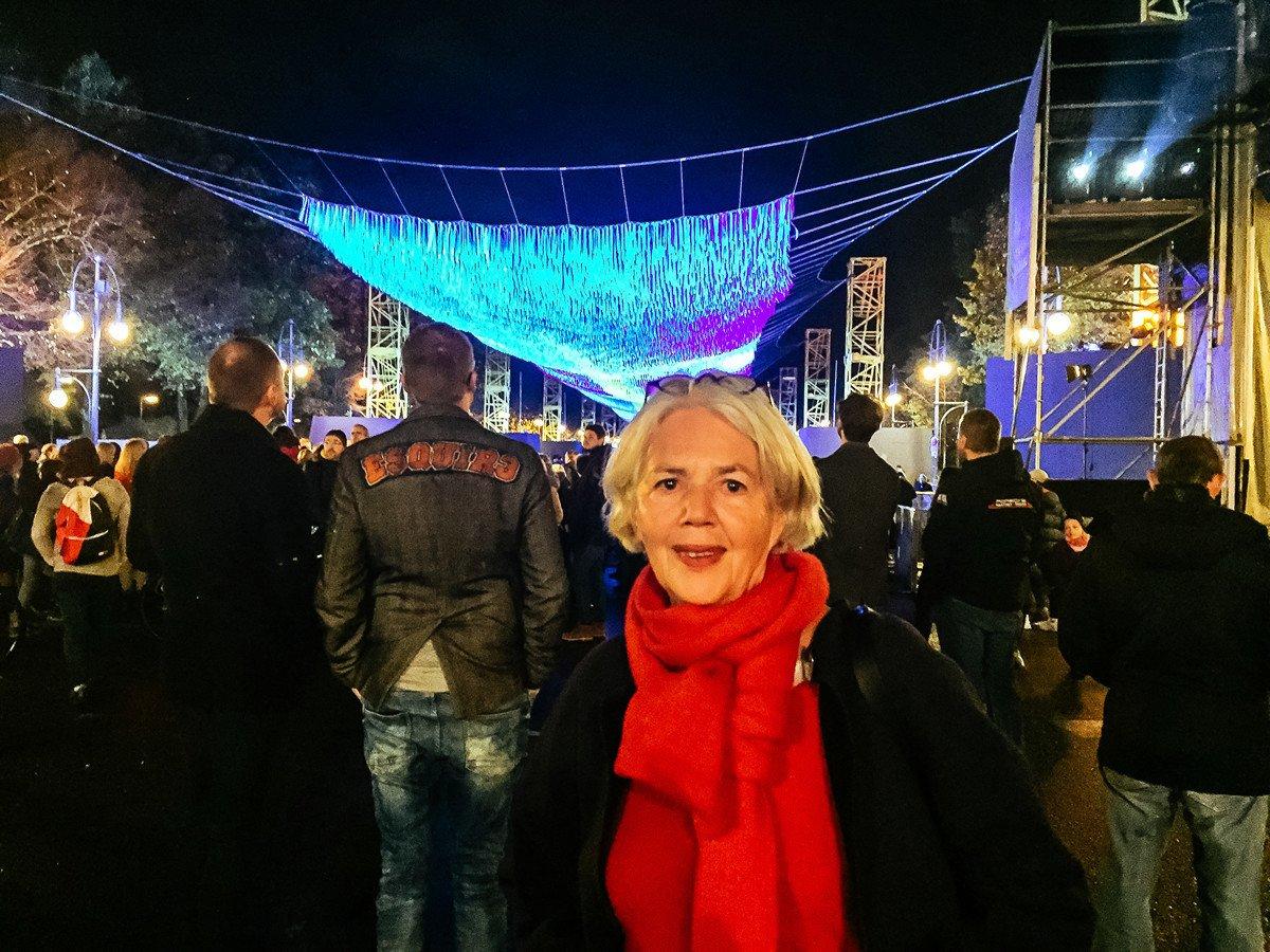已退休的耶娜在勃蘭登堡門前參觀柏林圍牆倒塌30周年的藝術作品「天網」。(穆華/大紀元)