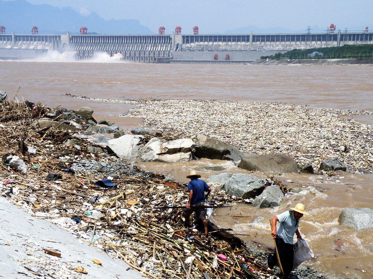 2010年8月1日,長江三峽大壩附近的江面上漂浮的大量垃圾,岸邊有兩名工人正在清理垃圾。(STR/AFP/Getty Images)