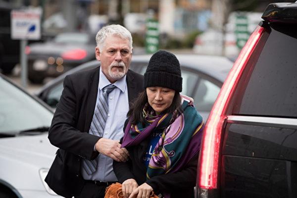 2018年12月獲准保釋後的華為CFO孟晚舟,在安保陪同下出門。(大紀元資料室)