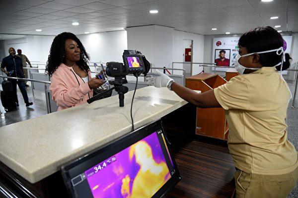 圖為尼日利亞拉各斯的穆爾塔拉·穆罕默德國際機場(Murtala Mohammed International Airport)熱掃瞄儀旁邊的港口健康服務工作人員。(PIUS UTOMI EKPEI / AFP)