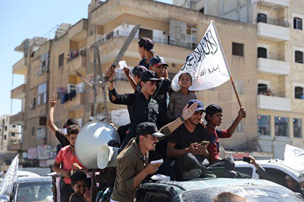 2021年8月20日,曾隸屬於阿蓋達組織的敘利亞聖戰組織 「沙姆解放組織」(Hayat Tahrir al-Sham)的成員,舉著他們的旗幟和塔利班成立的「阿富汗伊斯蘭酋長國」的旗幟遊行。(OMAR HAJ KADOUR/AFP via Getty Images)
