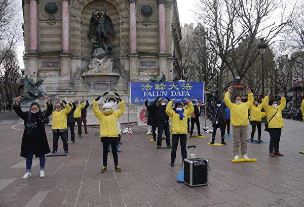 在巴黎聖米歇爾廣場上,法輪功學員集體煉功、展示功法。(明慧網)