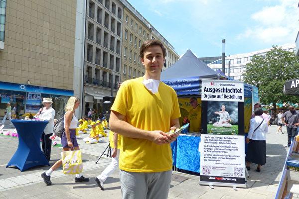 房地產顧問諾亞·施密特(Noah Schmidt)參與德國北威州法輪功學員在首府杜塞爾多夫市中心舉行和平紀念活動。(莫凌、Anh Hoang/大紀元)