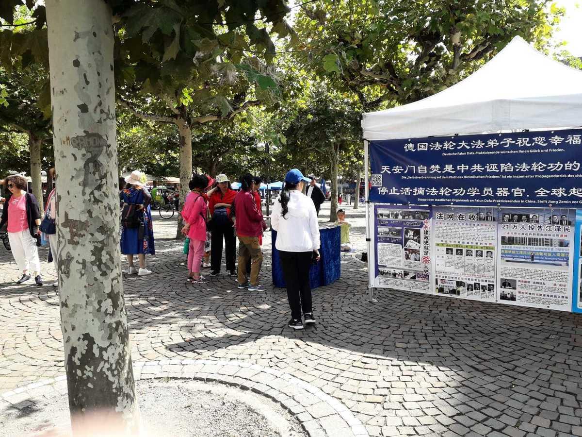 中國遊客在德國景點了解法輪功真相。(明慧網)
