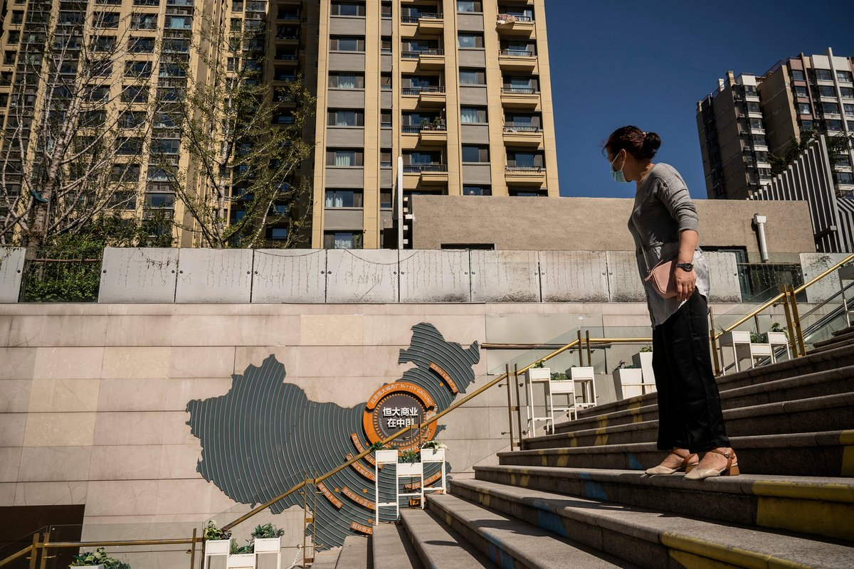 《華爾街日報》2021年9月23日引述知情人士的消息說,中共政府不願意救助最大的中國地產商恒大,地方官員已收到指令,為即將而來的暴風雨做好準備,同時監控民情。圖為2021年9月22日,在中國北京的恒大城市廣場購物中心,一名女子正路過恒大的廣告牌。(Andrea Verdelli/Getty Images)