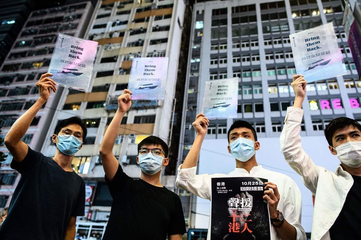 2020年10月20日,黃之鋒(左二)和其他民主活動人士在香港舉牌,呼籲釋放被扣押在中國大陸的12港人。(ANTHONY WALLACE/ Getty Images)