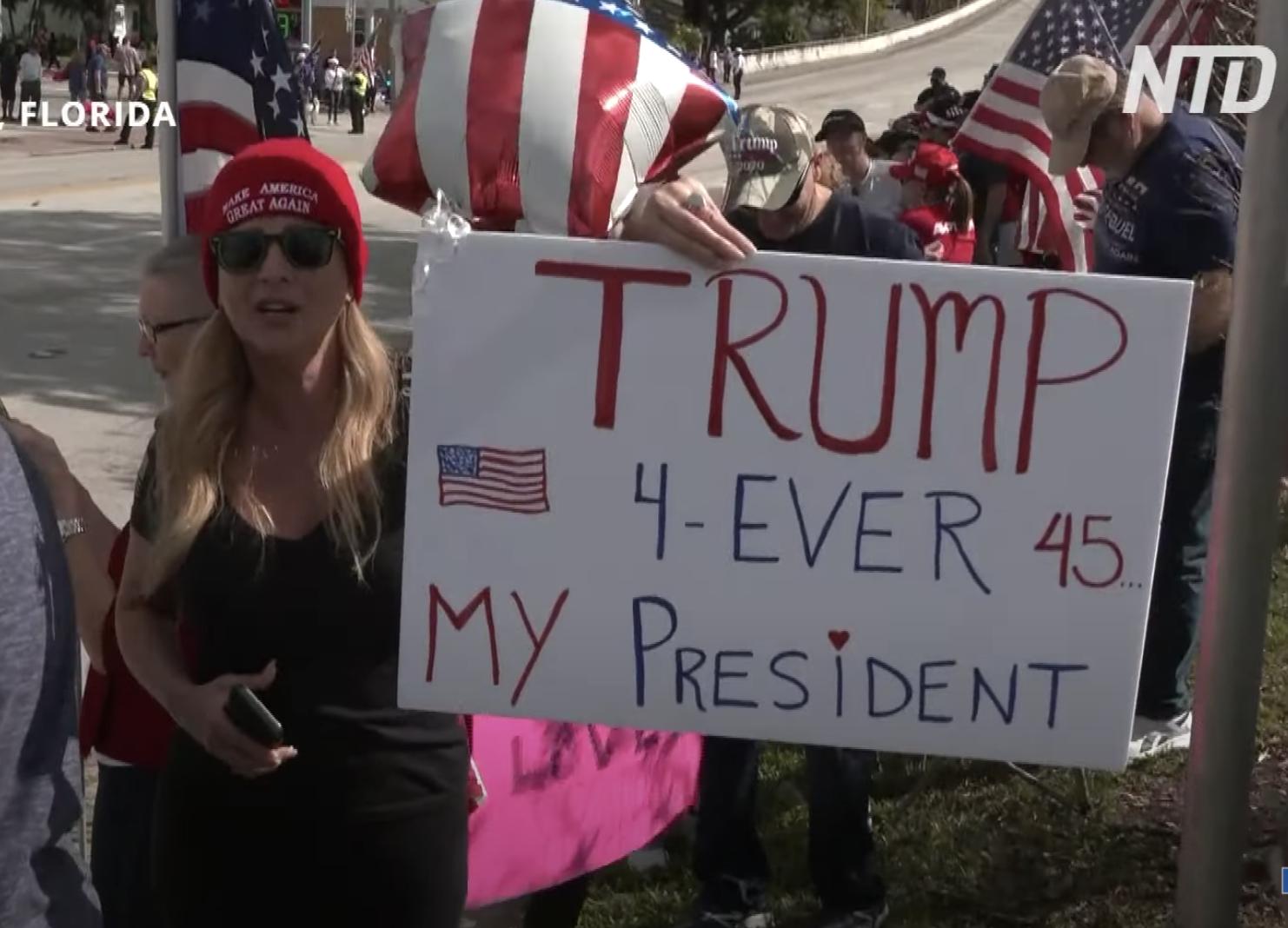 1月20日,佛州一名女子站立在靠近佛州海湖莊園(Mar-a-Lago)附近街道兩旁,打著「特朗普永遠是我的總統」標語牌,歡迎特朗普回到佛州。(新唐人)