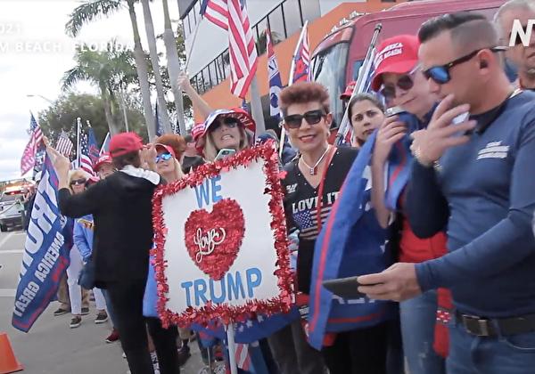 2021年1月20日,很多民眾在靠近佛州海湖莊園(Mar-a-Lago)附近街道兩旁站立,他們戴著「讓美國再次偉大」的帽子,舉著美國國旗,打著「我們愛特朗普」、「特朗普是史上最好總統」、「神祝福您」等標語牌,夾道歡迎特朗普回到佛州。(新唐人電視台)