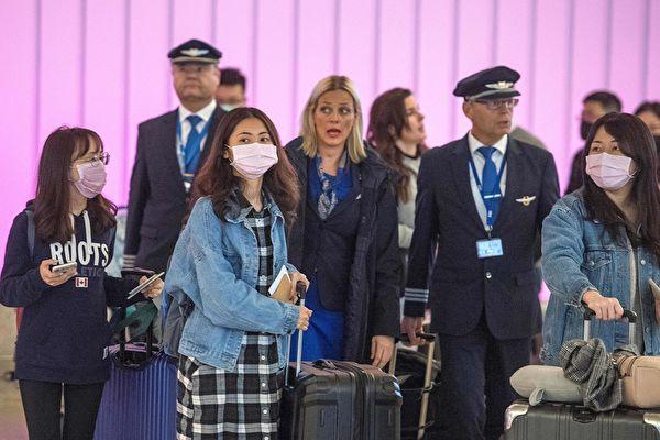 中共肺炎爆發,並蔓延全球。圖為戴著口罩抵達洛杉磯國際機場的旅客。(MARK RALSTON/AFP via Getty Images)