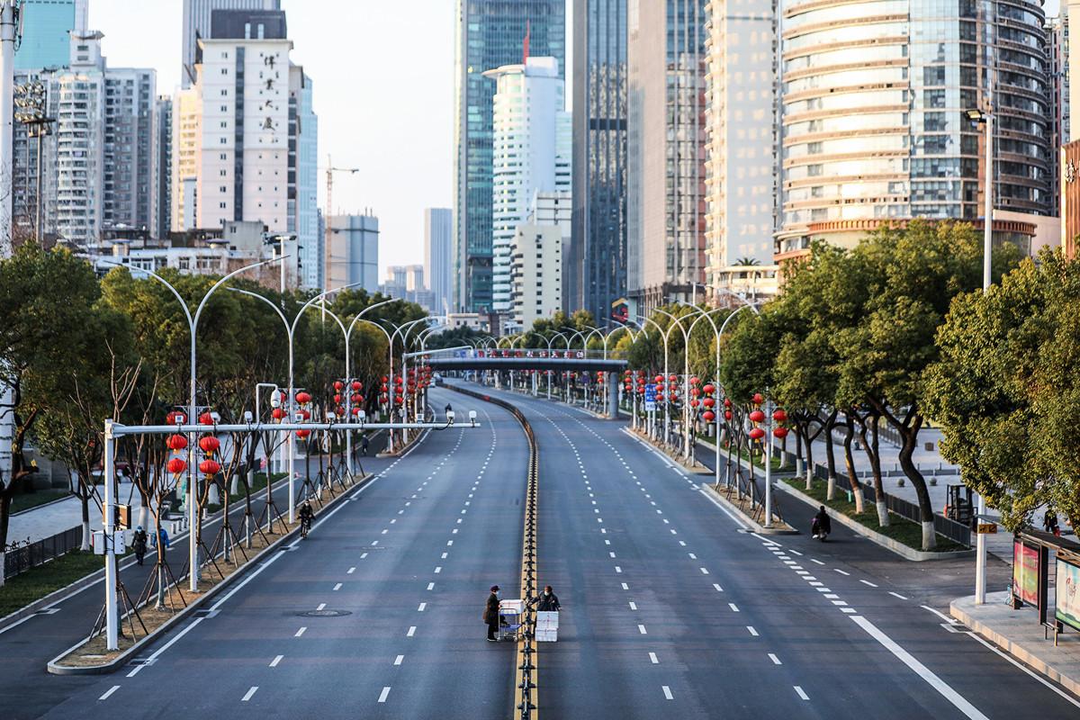 圖為2020年2月20日,兩名工作人員運送蔬菜到武漢市的一家醫院,越過一條空空盪盪的大馬路。( STR / AFP ) / China OUT