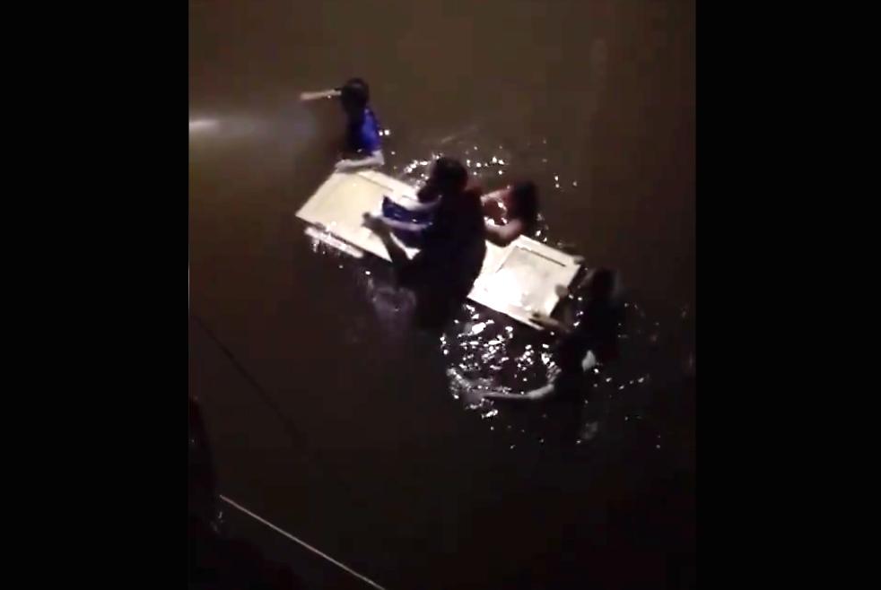 7月22日晚間,河南輝縣吳村鎮多日暴雨,水庫急洩,民眾乘門板水上漂,等待救援。(影片截圖)