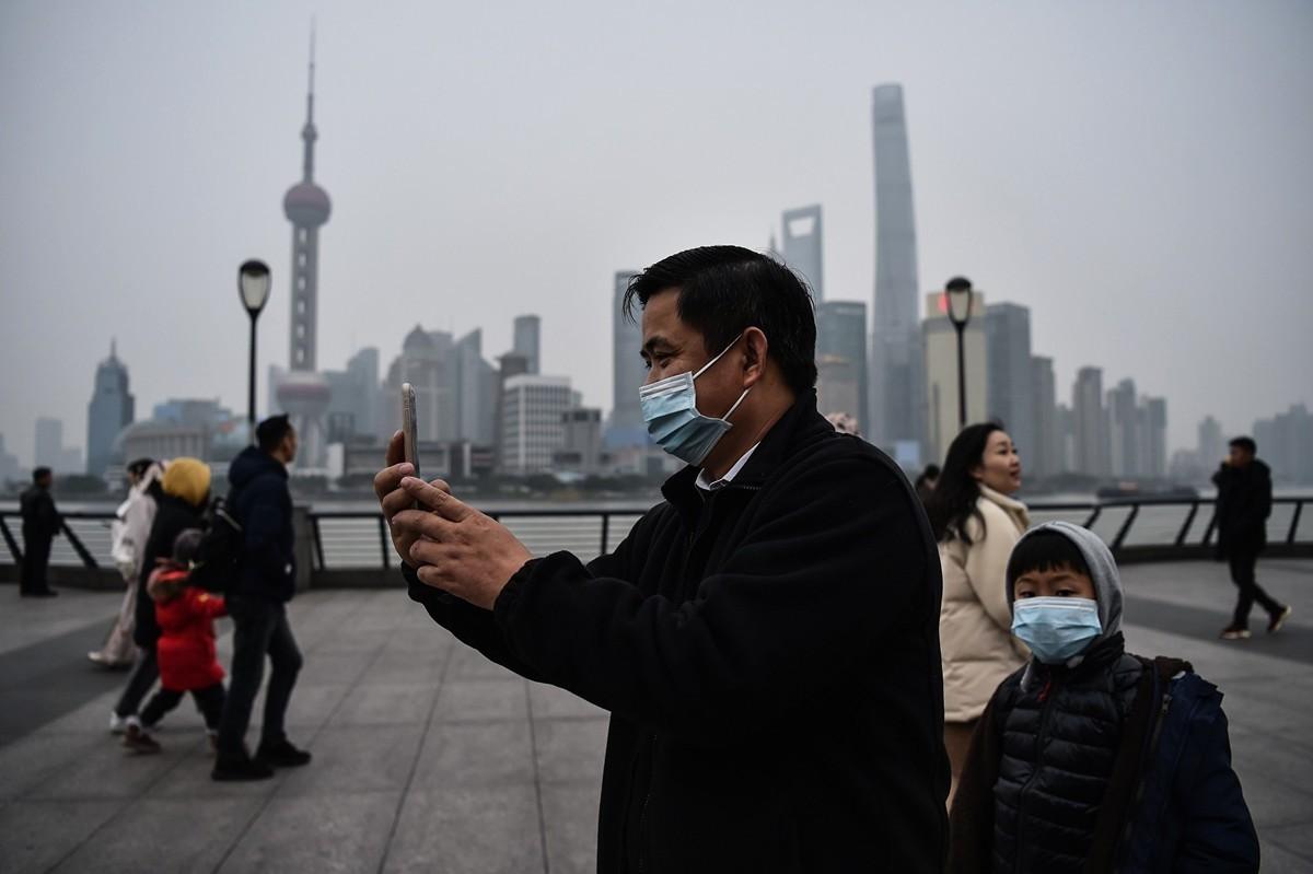 2020年1月21日,上海一名戴口罩的男子在玩自拍。(HECTOR RETAMAL/AFP via Getty Images)