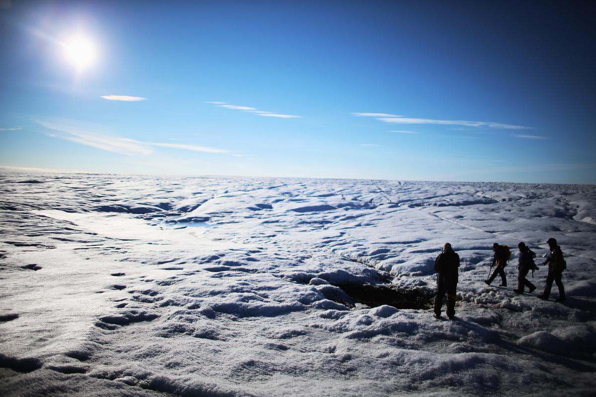 圖為2013年7月15日,在格陵蘭的冰原上,來自伍茲霍爾海洋研究所和華盛頓大學的科學家走過冰川。(Photo by Joe Raedle/Getty Images)