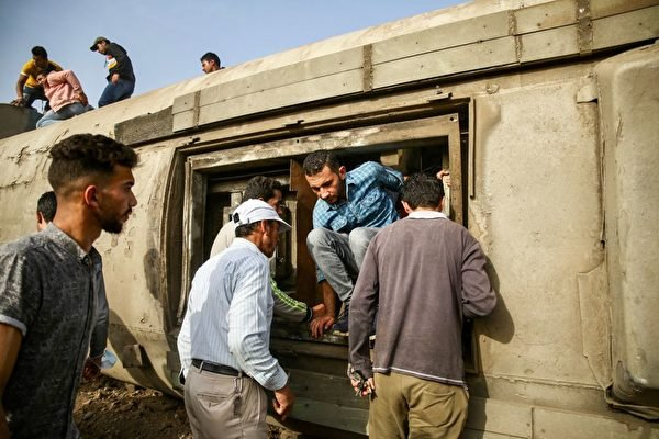 一名乘客從翻倒的火車車廂內跳出來。(AYMAN AREF/AFP via Getty Images)