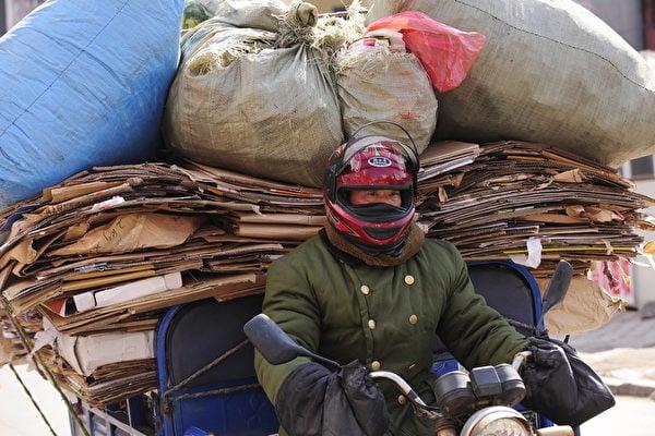 東北經濟面臨兩大危機:從外部來說,沒人願意投資東北;從內部來看,東北的企業停止發展,消極度寒冬。圖為吉林省延吉市的一名騎機車的資源回收男子。(PETER PARKS/AFP)