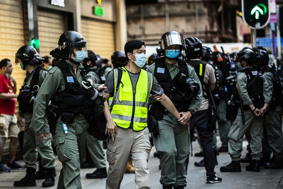 圖為在港人抗議中共國安法期間,港警抓捕一名男子。(Photo by ISAAC LAWRENCE/AFP)