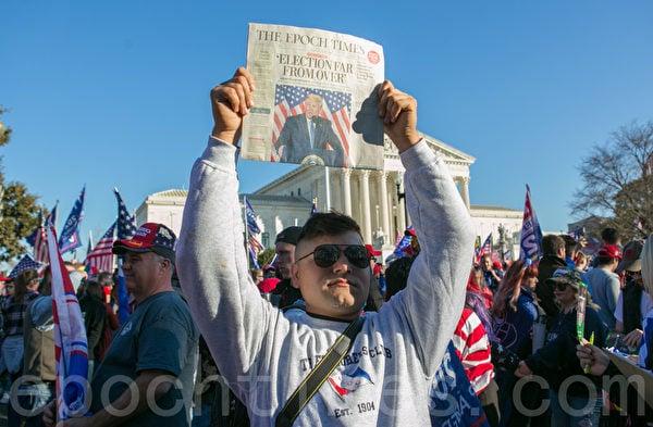 2020年11月14日,在華盛頓DC,一位參加制止竊選(Stop the Steal)大遊行和集會的民眾高舉《大紀元時報》頭版的報道支持特朗普總統。(李莎/大紀元)