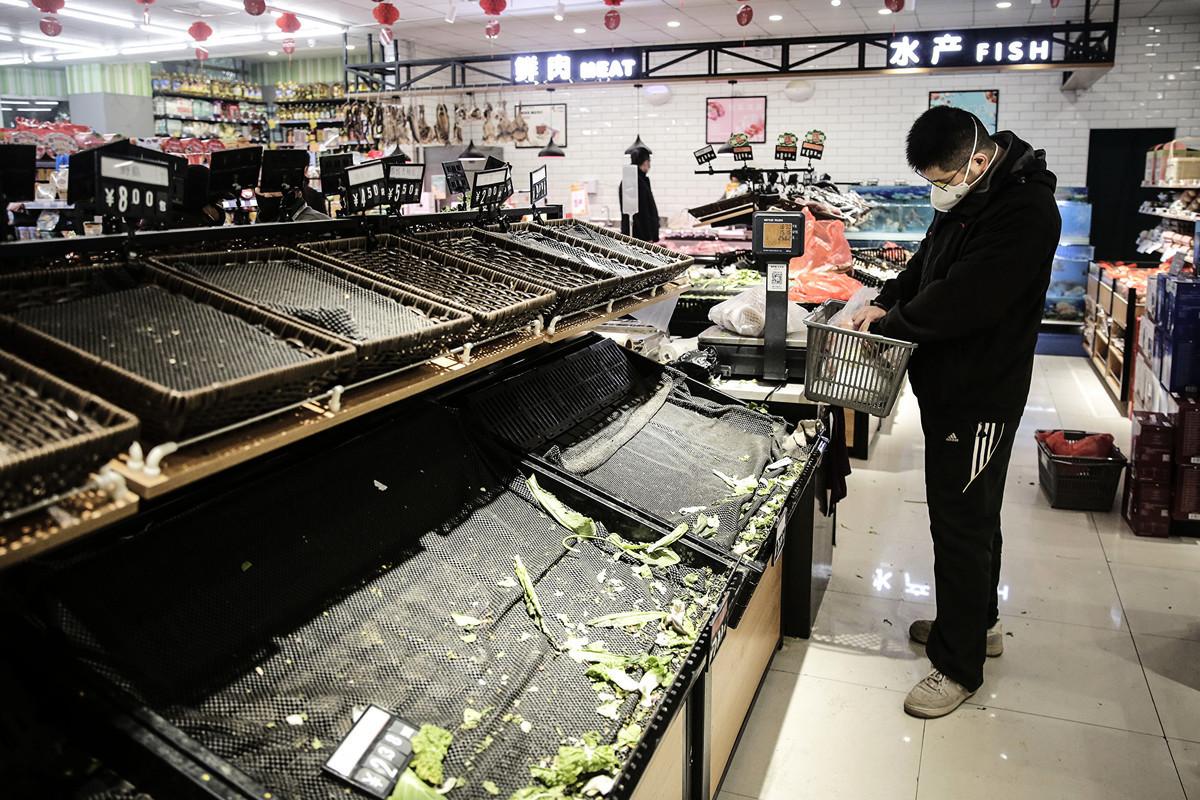 武漢封城後,市民一律不得離開武漢。圖為2020年1月23日,武漢市民戴著口罩在超市買菜。(Getty Images)