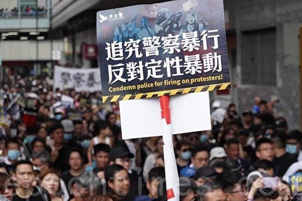 2019年7月14日,香港沙田大遊行,民眾持各種標語表達訴求。圖為「追究警察暴行 反對定性暴動」的標語。(余鋼/大紀元)