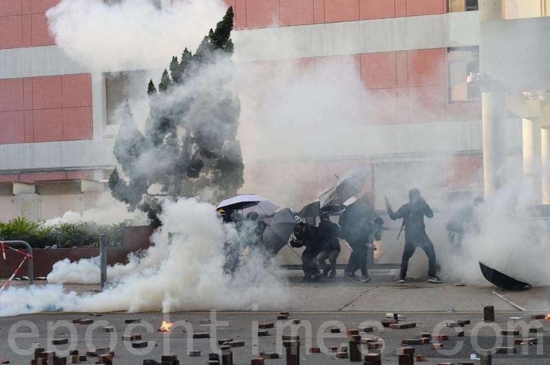 2019年11月18日早上,理大抗爭者約好外撤,被防暴警察用催淚彈攻擊,又不得不退回校園內。(宋碧龍/大紀元)