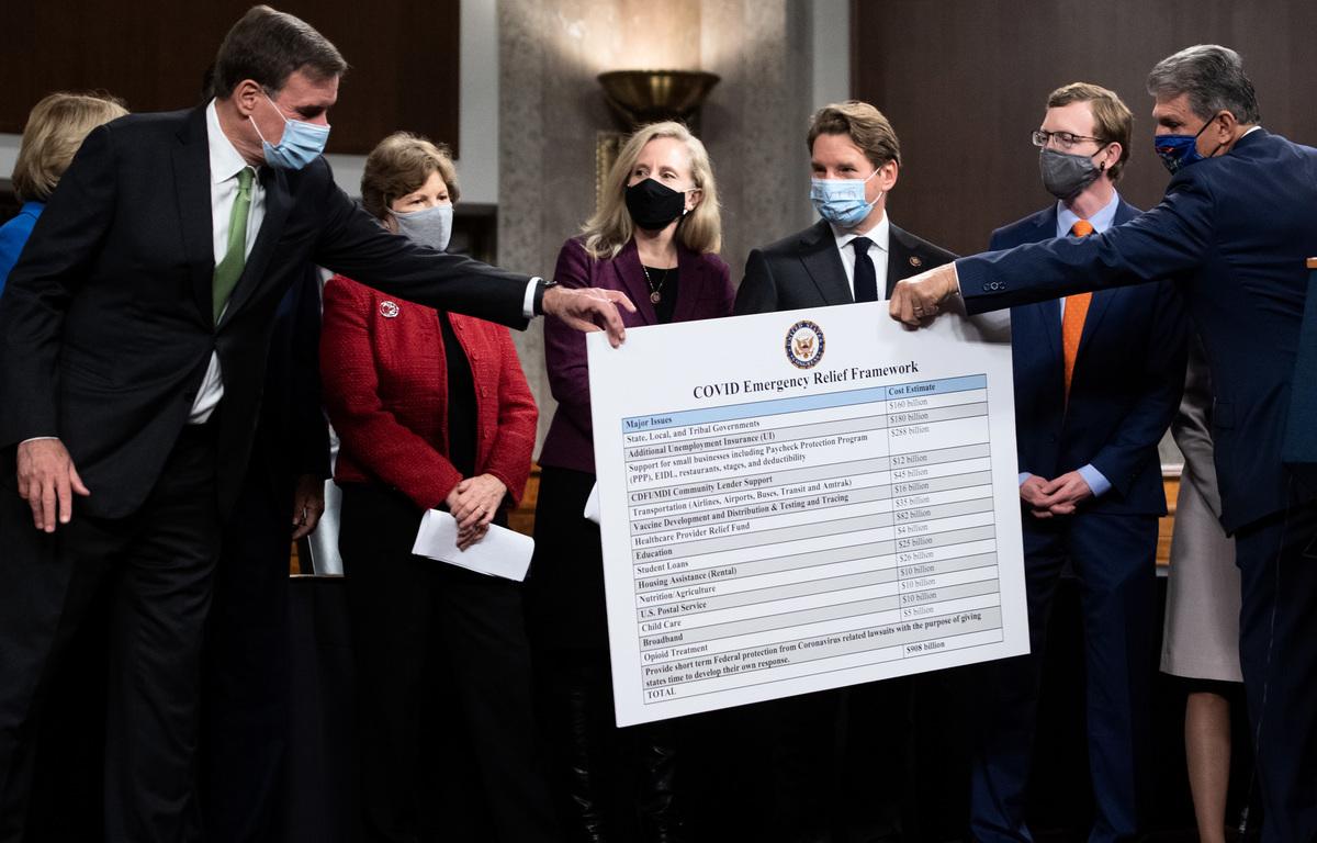 2020年12月1日,美國西維珍尼亞州民主黨參議員喬·曼欽(Joe Manchin,右)在新聞發佈會上,將一張描述救濟法案的海報遞給參議員馬克·華納(Mark Warner,左)。(SAUL LOEB/AFP via Getty Images)