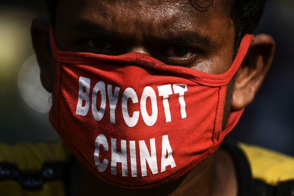 近來,一群印度裔美國人在中國領事館前舉行了和平示威,抗議中共藉著病毒大流行之際,對印度進行侵略。圖為在印度的一名司機,戴著抵制中國(中共)的口罩。(SAJJAD HUSSAIN/AFP via Getty Images)