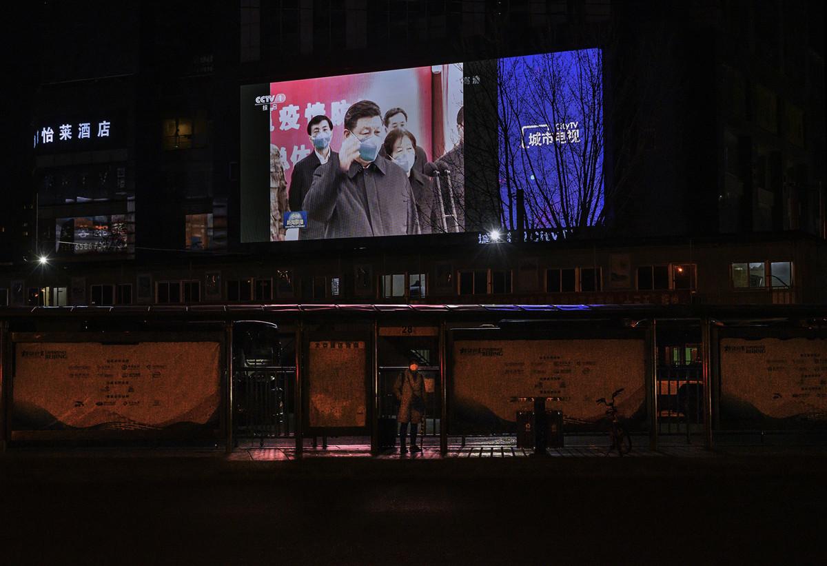 習近平3月10日乘飛機抵達湖北省武漢市考察中共肺炎疫情。圖為北京大街上屏幕上的報道。(Kevin Frayer/Getty Images)