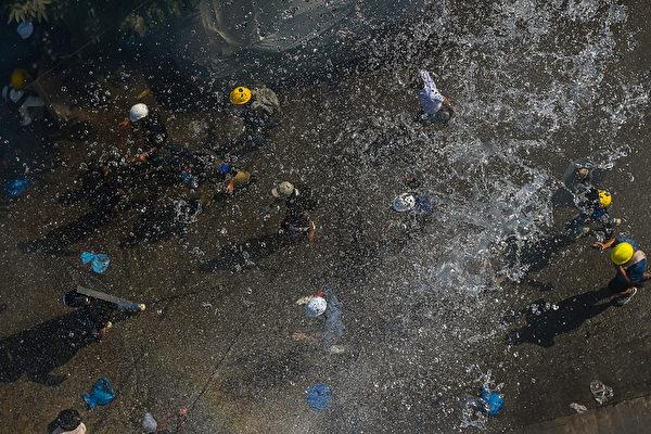 2021年3月8日,仰光民眾在街頭抗議軍事政變活動中,武警不僅發射催淚彈之後,又向民眾放水。(STR/AFP via Getty Images)