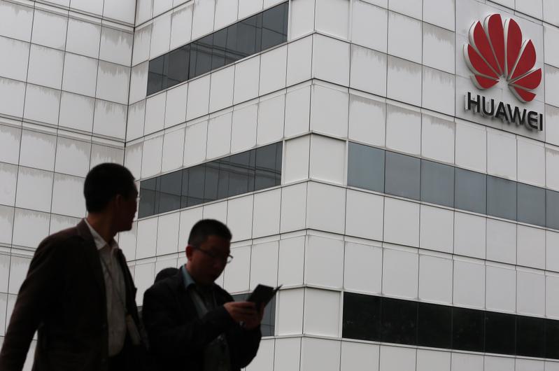圖為兩位男士經過華為在深圳的辦公大樓。(Getty Images)