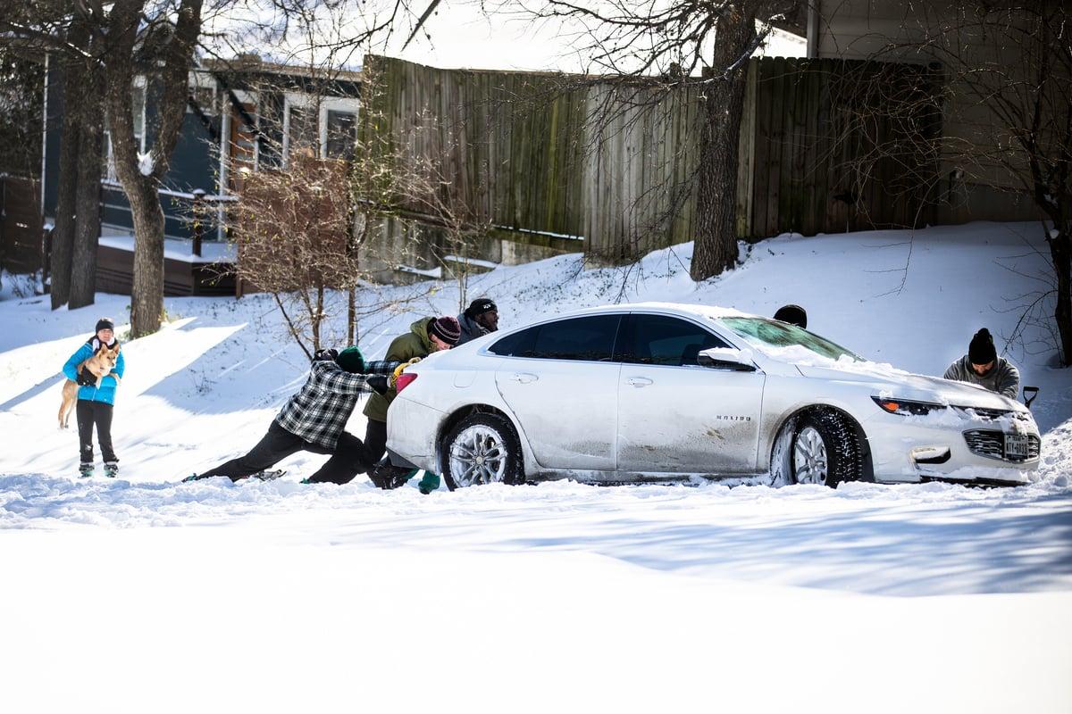 2021年2月15日,德薩斯州奧斯汀居民將汽車從雪中推著前行。(Montinique Monroe/Getty Images)