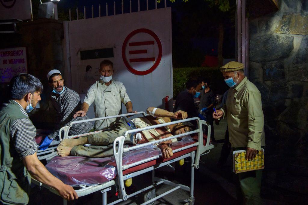 8月26日,阿富汗喀布爾機場外發生自殺炸彈襲擊。圖為醫務人員將受傷男子抬上擔架。(WAKIL KOHSAR/AFP via Getty Images)