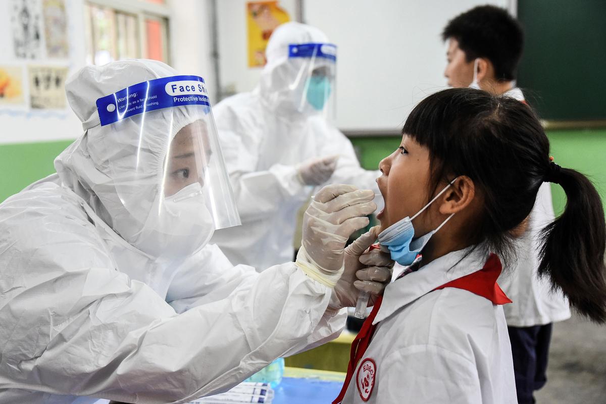 2020年8月17日河北省邯鄲市的醫務人員正在採集小學生的口咽拭子樣本。外界注意到,很多大陸醫務人員操作不規範,採集拭子樣本時觸及受檢者的肢體易出現交叉感染。( STR/AFP via Getty Images)