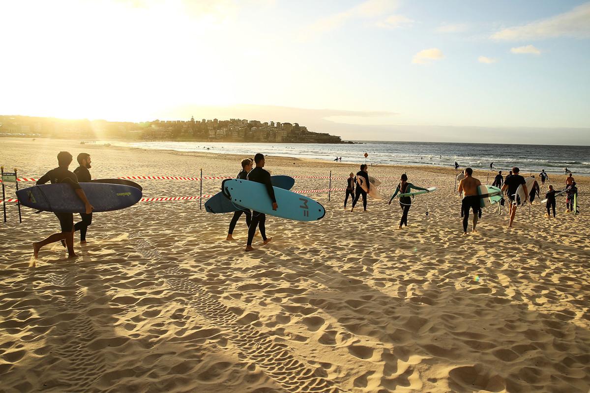 澳洲疫情與西方其它發達國家相比損失較小,有望成為最先脫離中共肺炎大瘟疫的國家之一。圖為2020年4月28日清晨7點,悉尼Waverley市政府重新開放了著名的Bondi海灘,拿著衝浪板的人們走向大海。(Mark Kolbe/Getty Images)