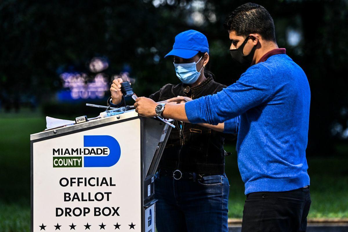 2020年11月3日,美國佛羅里達州邁阿密-戴德縣(Miami-Dade County),一名選舉工作人員(右)協助選民將她的票投入投票箱。(CHANDAN KHANNA/AFP via Getty Images)
