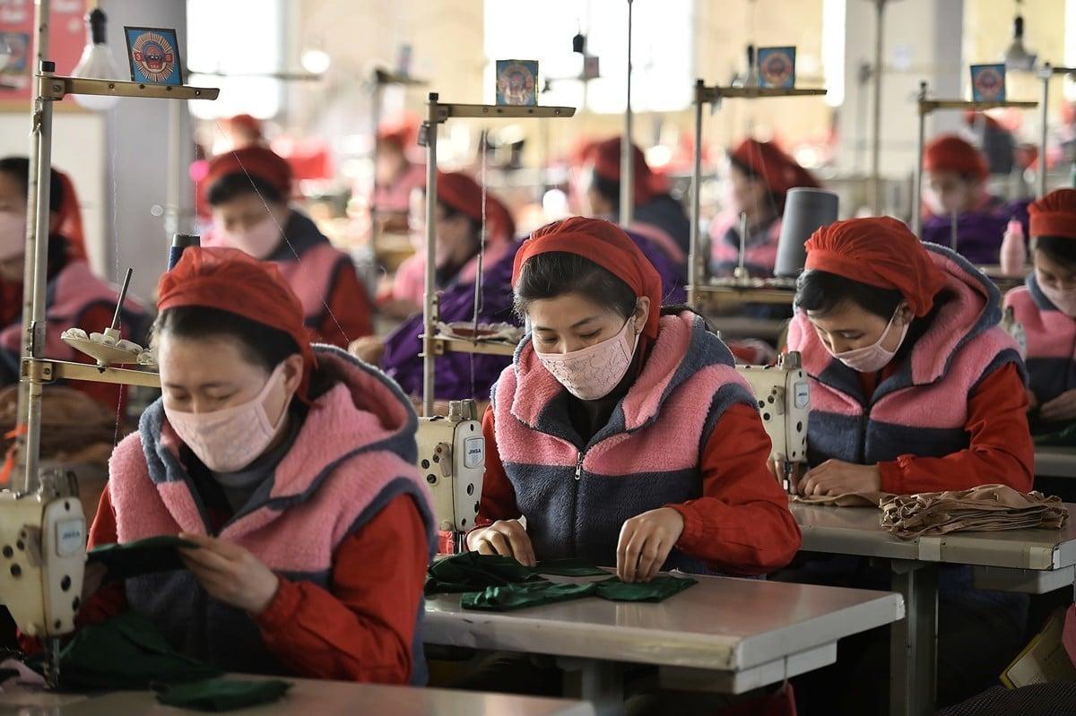 一名北韓官員因違反隔離禁令被槍決。圖為戴著防護口罩上班的北韓女工。(Kim Won-Jin/AFP)