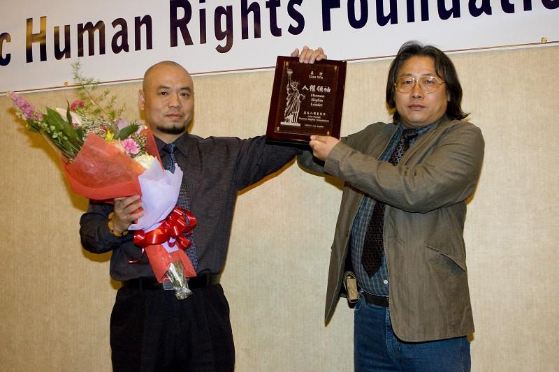圖為在營救鄧玉嬌過程中發揮重要作用的吳淦(左)獲頒「人權領袖獎」,發獎人為香港社運人士劉泰。(季媛/大紀元)