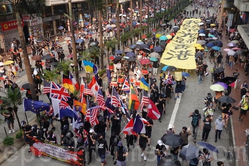 2019年9月29日,全球24個國家、65個城市舉行「全球連線-共抗極權」遊行。香港灣仔遊行隊伍,巨型橫幅經過,(余鋼/大紀元)