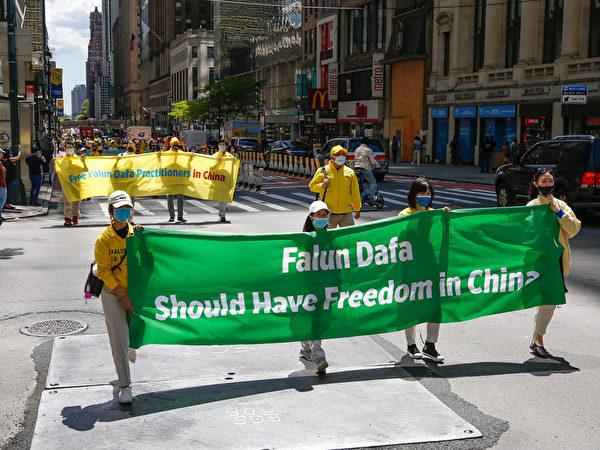 2021年5月13日,大紐約地區部份法輪功學員在曼哈頓舉行盛大遊行活動,他們以各式橫幅、旗幟及展板告訴人們真相,也呼籲中共停止迫害法輪功。(張靜怡/大紀元)